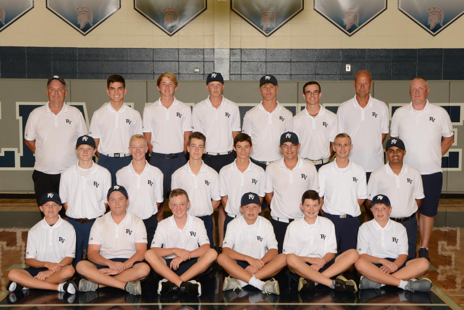 The boys golf team pose for their team picture.