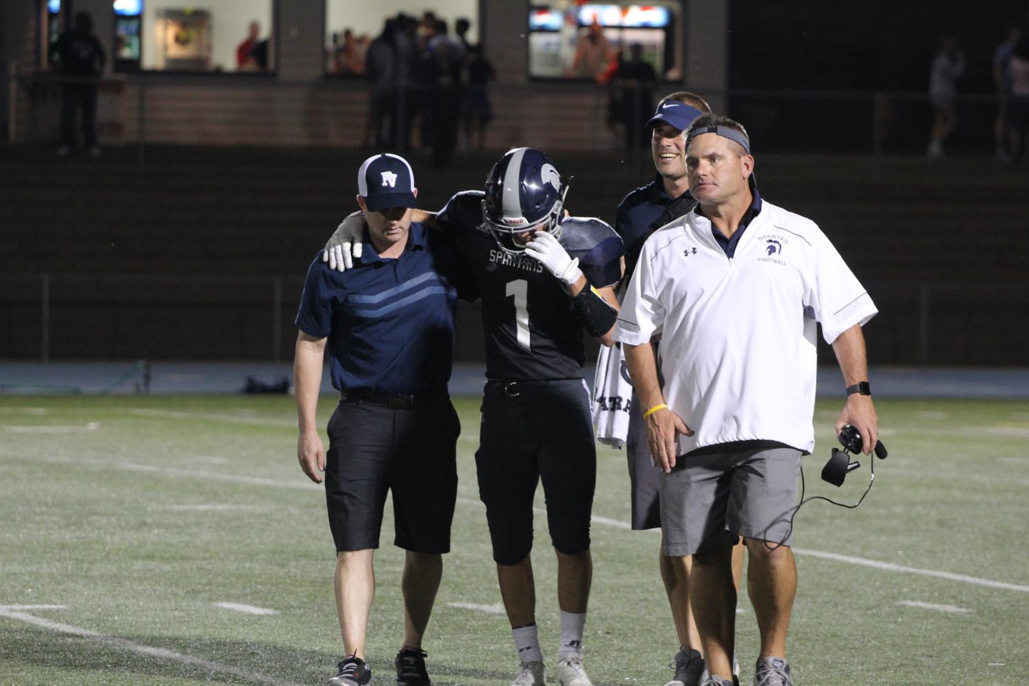Athletic trainer Jason Veal helps an injured athlete off of the field.