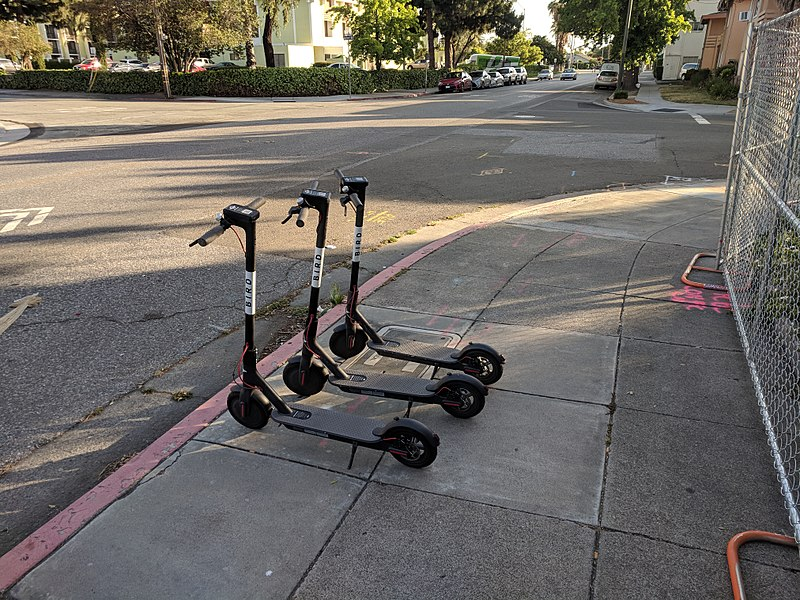 Three bird scooters available for use on the sidewalk.
