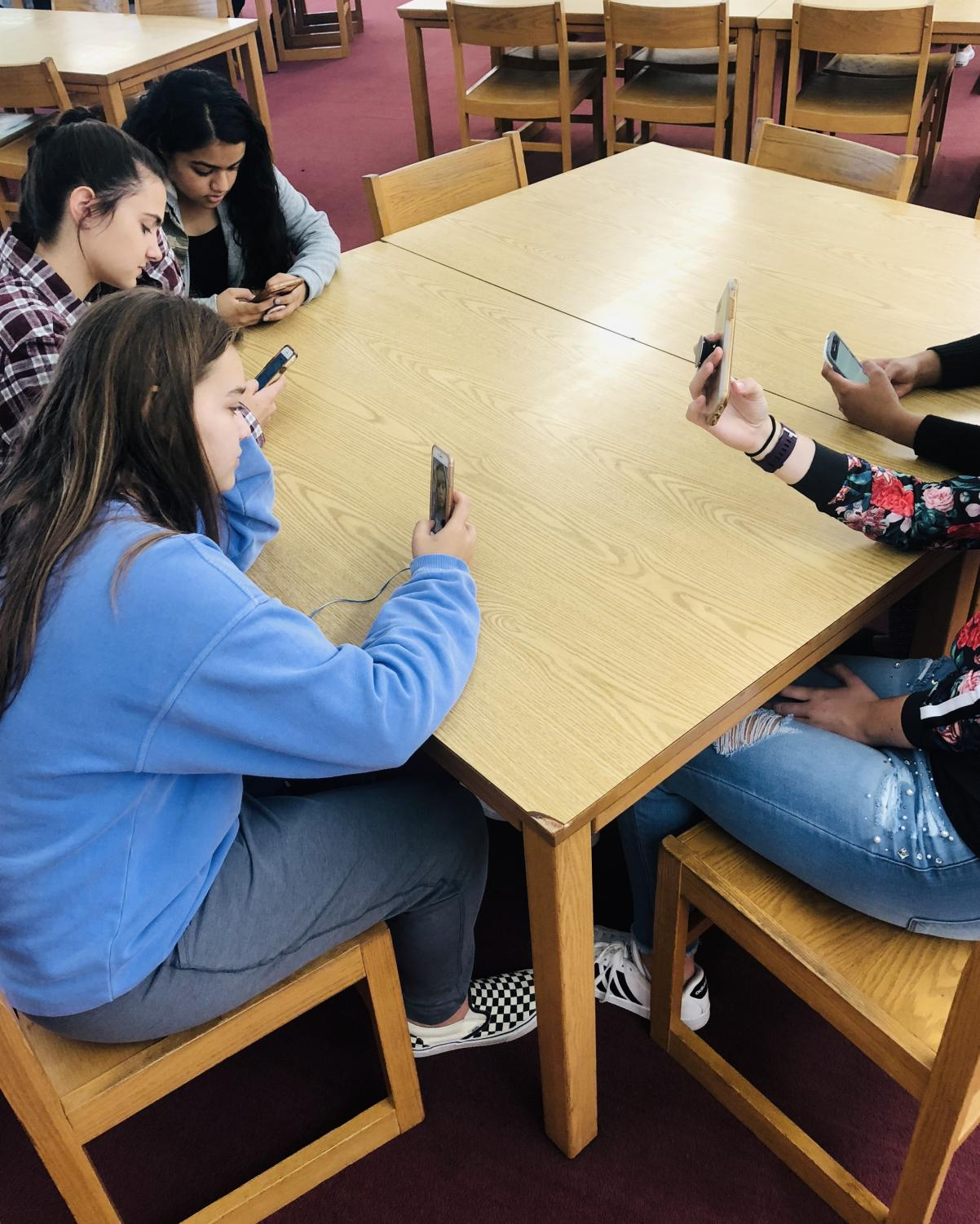 Students sitting on their phones instead of socializing.