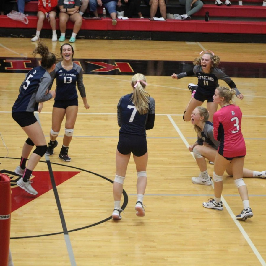 The Pleasant Valley volleyball team celebrates after winning.