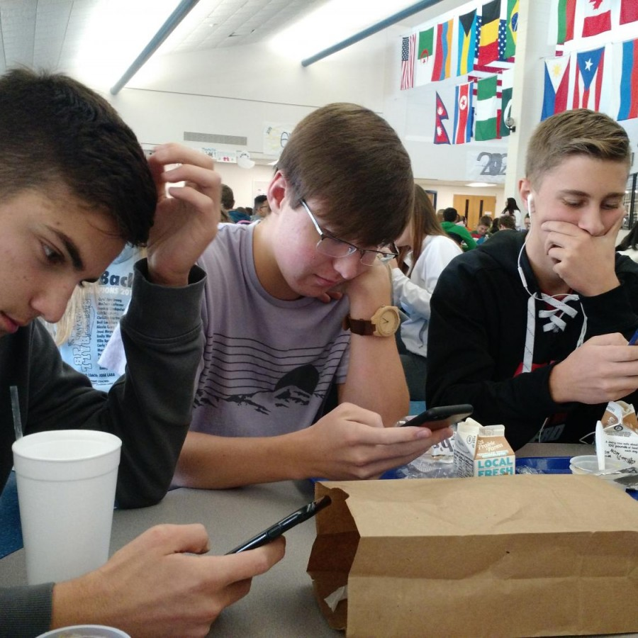 three+seniors+sit+on+their+phones+at+lunch.