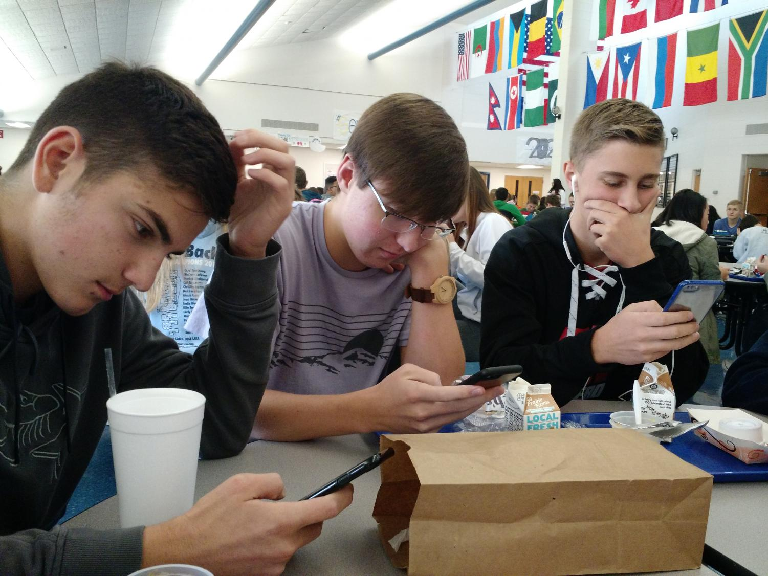 three seniors sit on their phones at lunch.