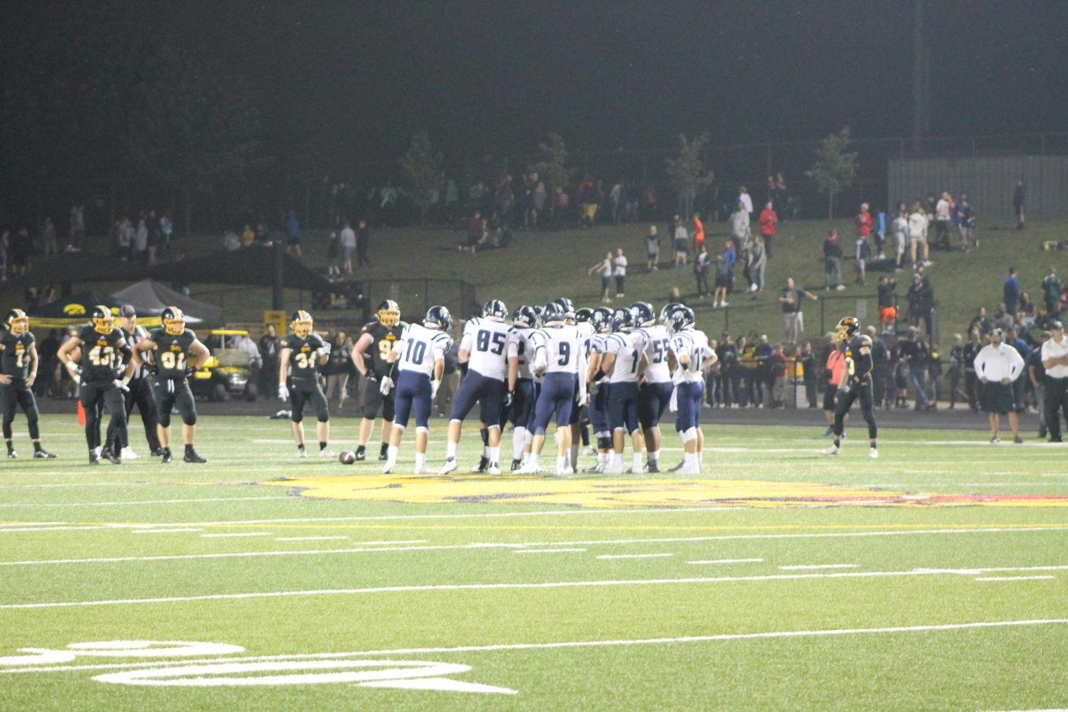 Spartans huddle together between downs while competing against hometown rival, Bettendorf.