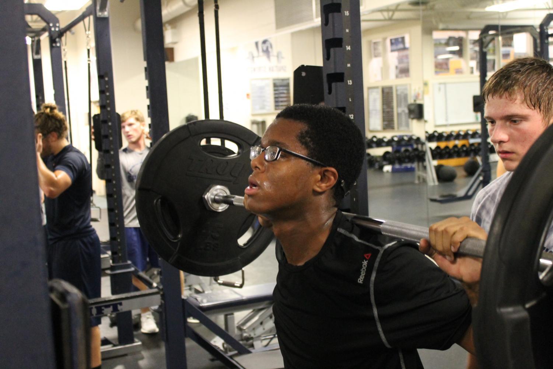 Senior Elijah Knauls squats while Senior Justin Sehlin spots him.