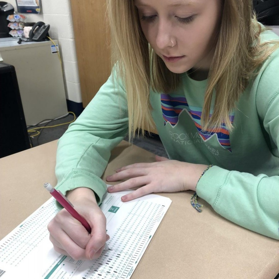 Student is filling out her answers for the Iowa Assessments.