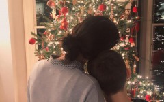 A loving Mom and her son gaze at the Christmas tree, enjoying the magic of Christmas by being together.