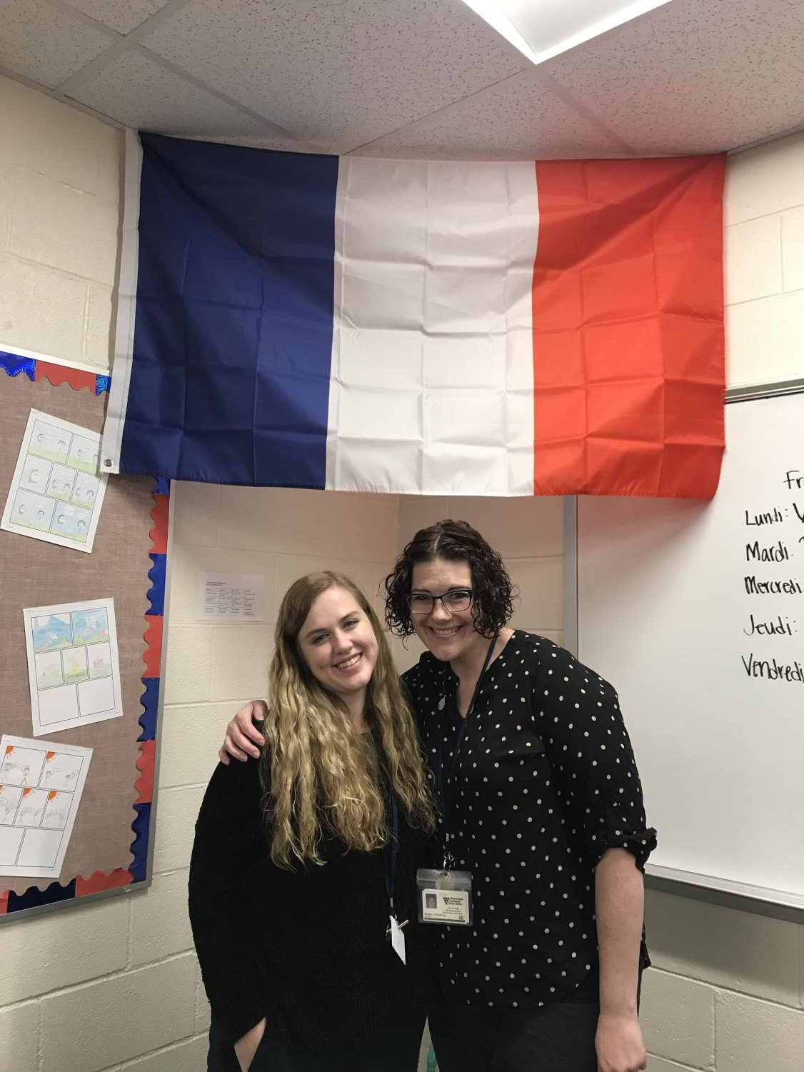 French Club teachers Melissa Lechtenberg and Marina Boes pose in front of Fance's signature flag