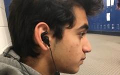 Junior wears earbuds in the hallway.