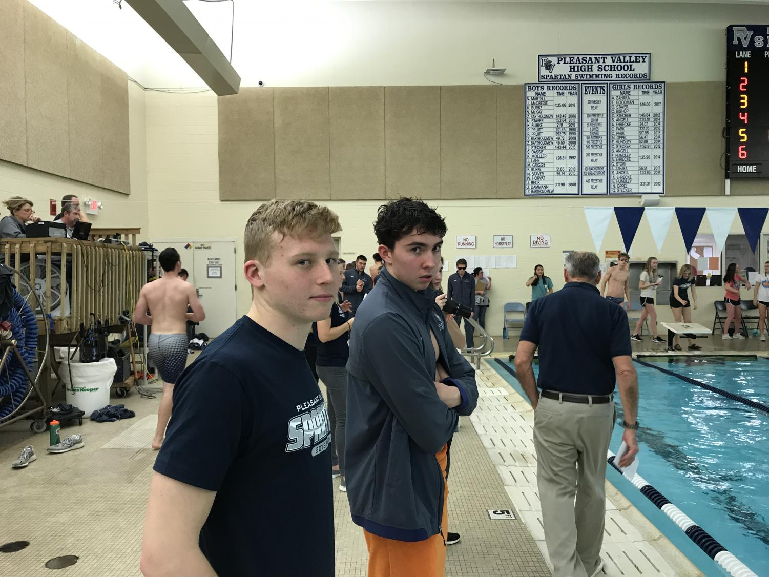 Senior captains Jacob Mccredie and Kevin Burke catch the camera as they watch their teammates swim from the sidelines. The boys' swim team is in the middle of season currently and can be found racing other schools in the swimming pool at Pleasant Valley High School