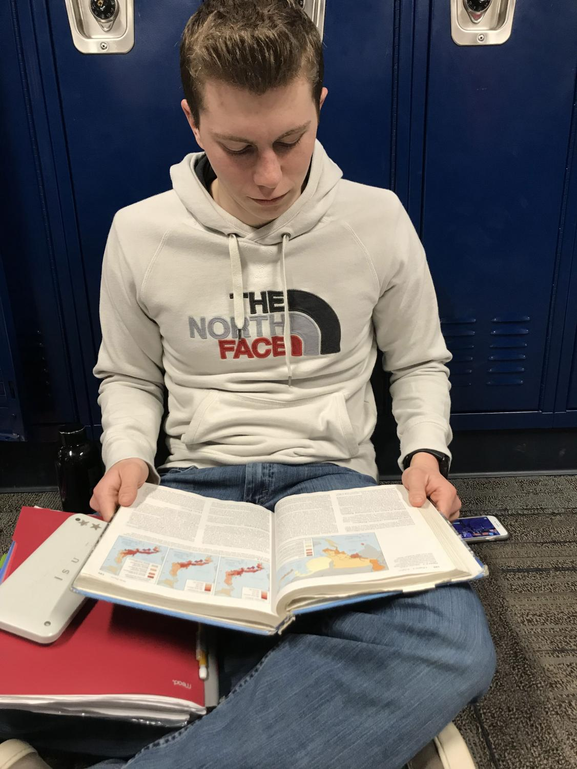 AP human geography student, Noah Streeter, reading the textbook to study for a test.
