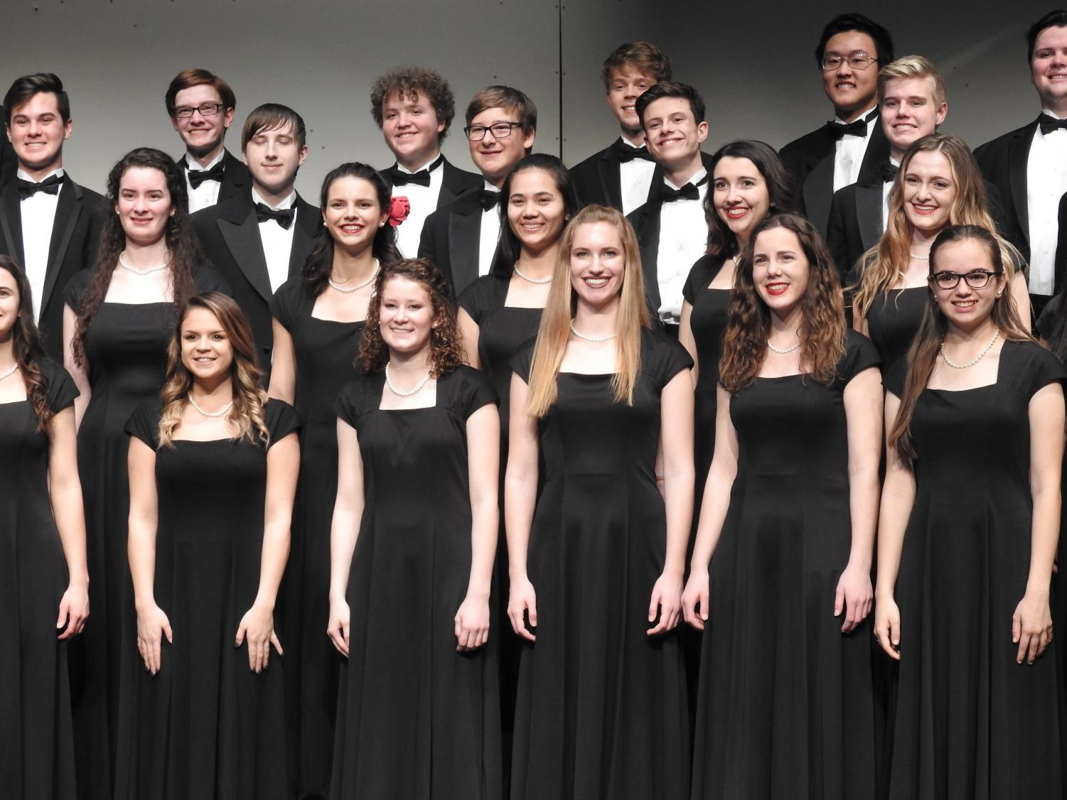 Some members of the 2018-19 PV Chamber Choir, standing stationary as they sing at a concert.