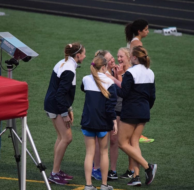 Athletes celebrating senior, Mallory Lafever's success in her individual race.