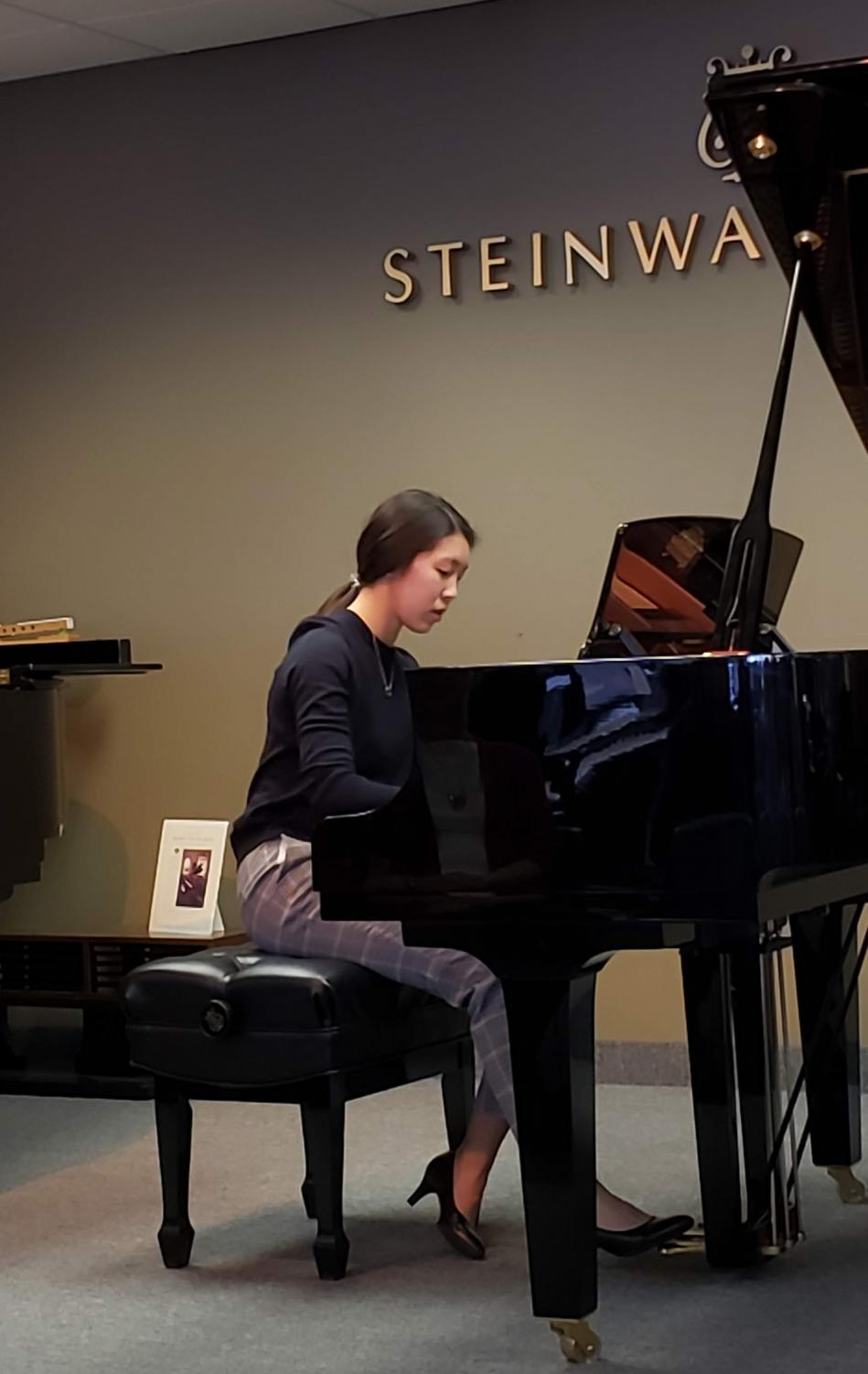 Christina Li playing the piano at a preparatory recital for a competition.
