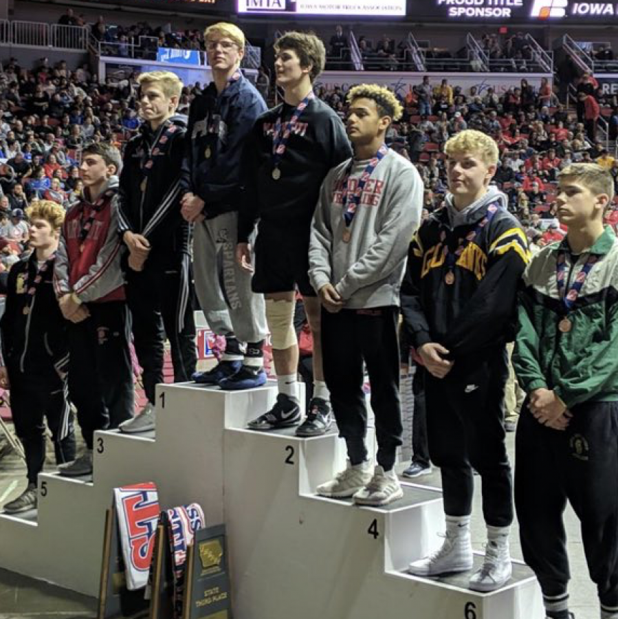 Eli+Loyd+with+his+fellow+competitors+after+winning+first+place+at+the+state+wrestling+tournament+in+Des+Moines.+%0A