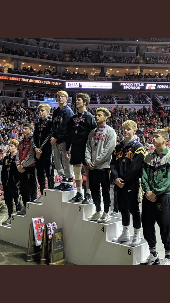 Eli Loyd with his fellow competitors after winning first place at the state wrestling tournament in Des Moines.