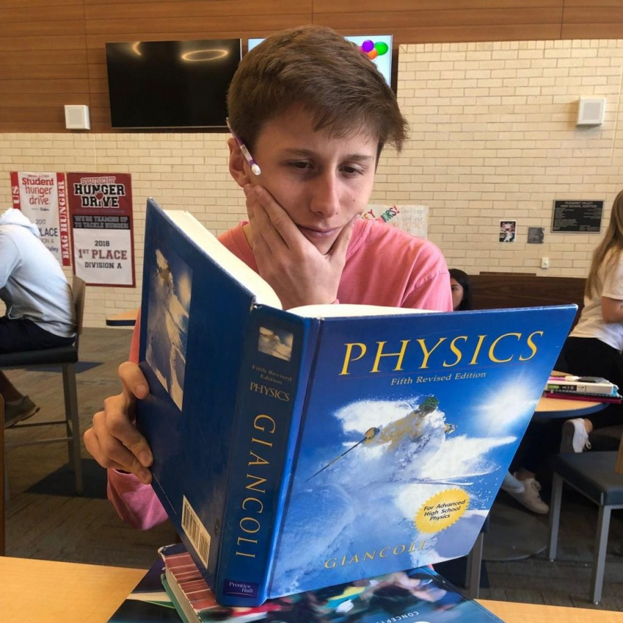 Senior, Jacob Bandy, reading books from three of his four AP classes he is taking currently.