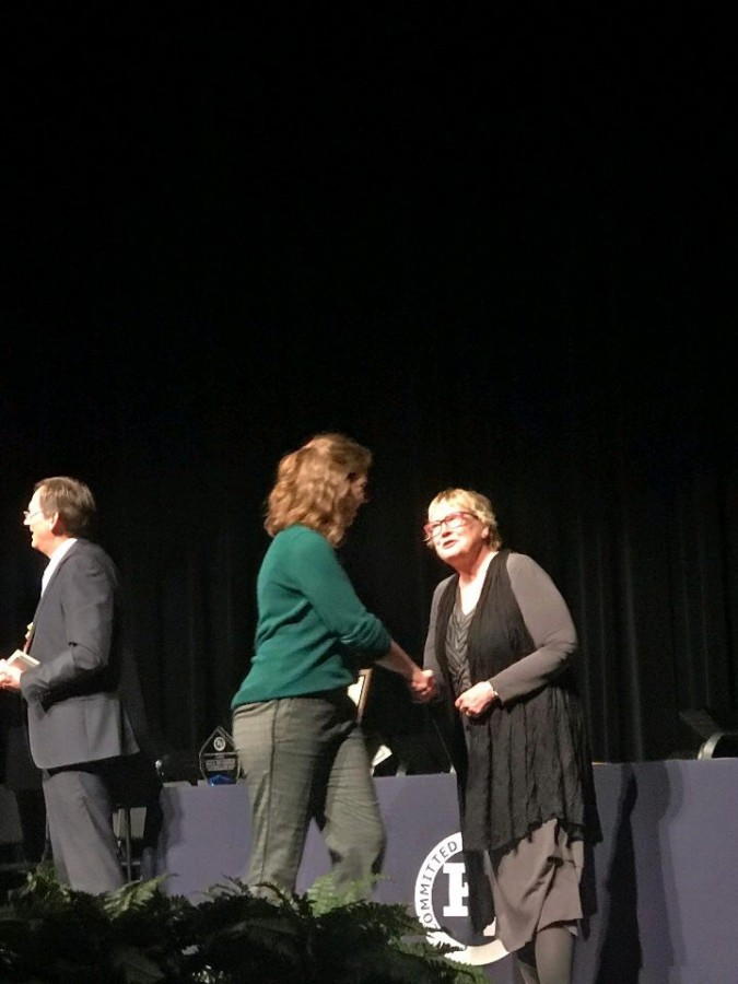 Kaitlyn Ryan shakes hands with Mike Zimmer and Michele Lynberg during the ceremony of Academic Awards night