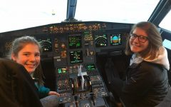 Sophie Malmen (left) and Trinity Malmen (right) sit in the cockpit of an airplane after their flight to Orlando, Florida.