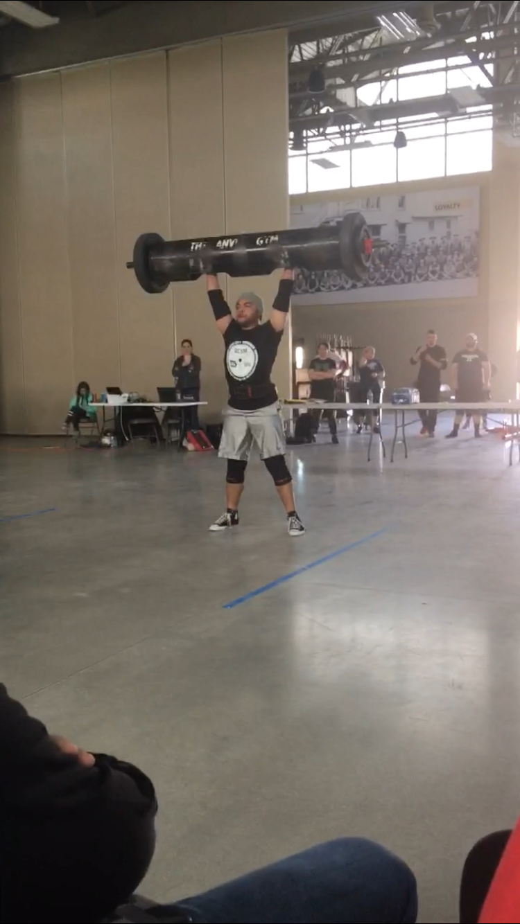 David Baxter competing in the log clean and press event, pressing 230 lbs.