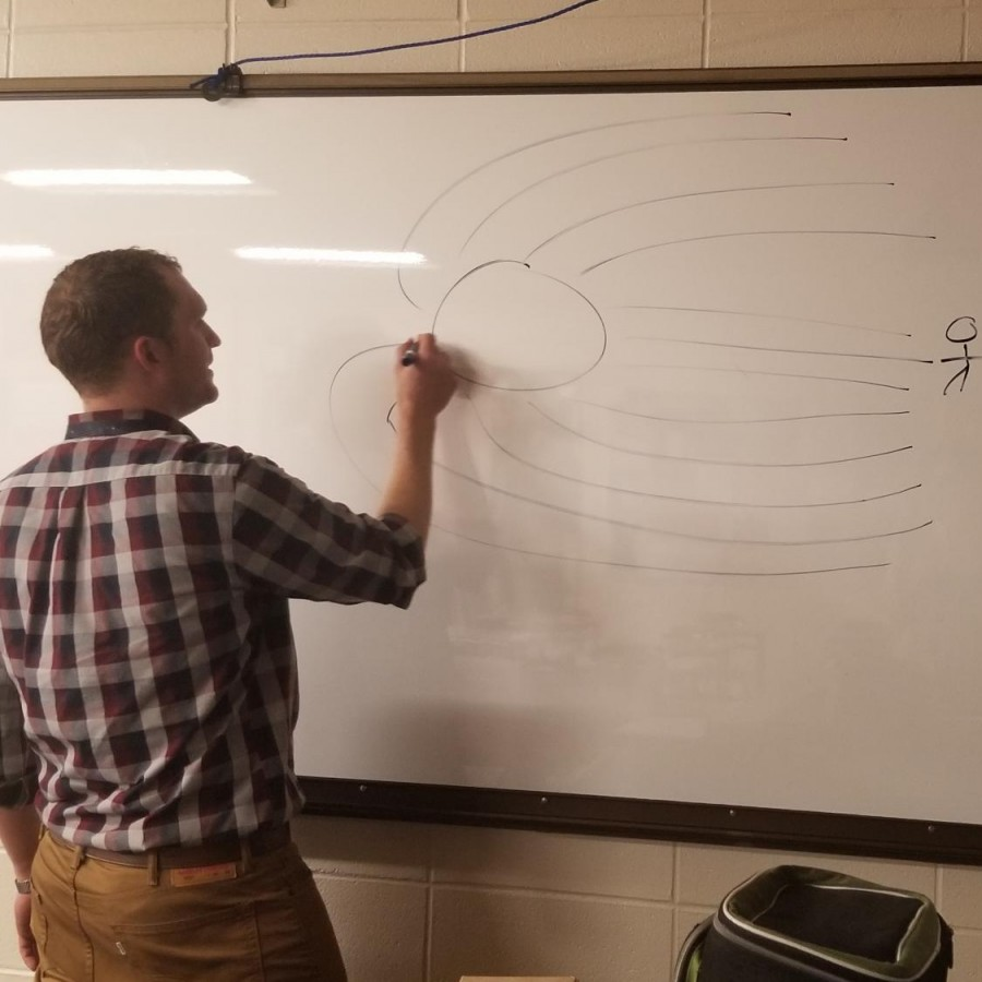 Ian+Spangenberg+draws+a+diagram+demonstrating+how+light+bends+when+close+to+a+black+hole.