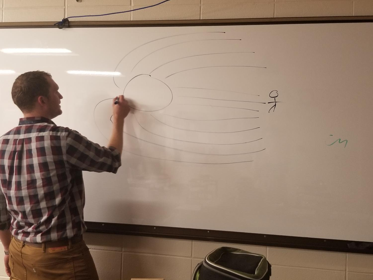 Ian Spangenberg draws a diagram demonstrating how light bends when close to a black hole.
