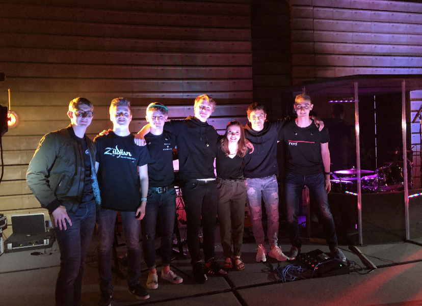 Trevor Glaum, Craig Richard, Sam Adams, Grant Ellingson, Alyse Zuiderveen, Josh Schmeichel, and Jonathan Glaum, shown left to right, on-stage before their performance at PV Palooza.