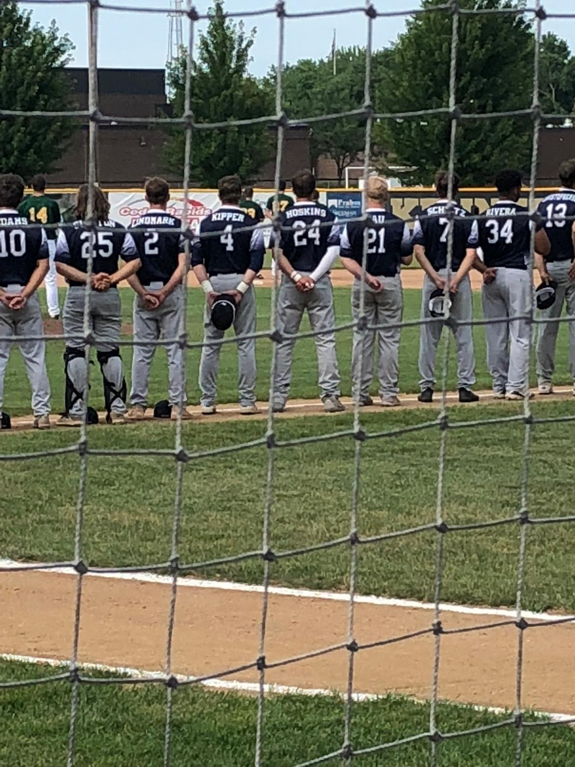 Pleasant Valley Baseball team standings for the national anthem before playing in the hot, summer heat.