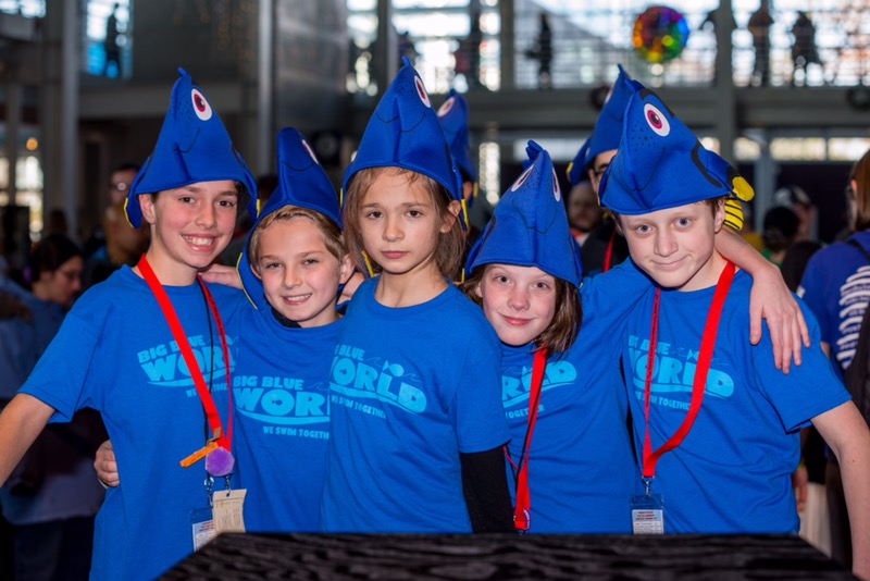 Big Blue World members sport both team shirts and smiles while at a robotics competition.