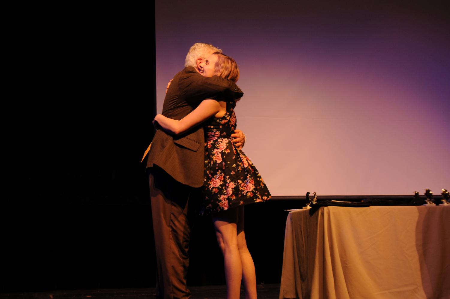 Freshmen, Harper Clark, hugging Director Bill Myatt after being inducted into the Thespian Honor Society.