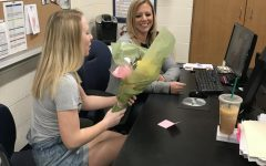 Student Maya McClain hands teacher, Maureen Dyer, flowers for teacher appreciation week.