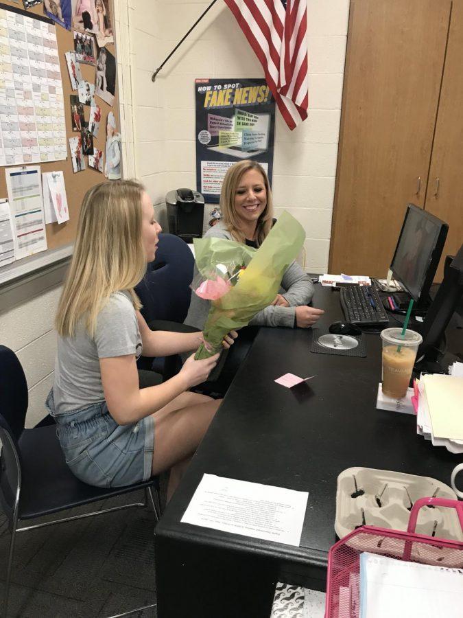 Student Maya McClain hands teacher, Maureen Dyer, flowers for teacher appreciation week.