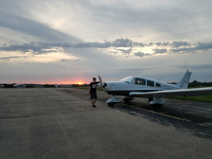 Rian O'Hanlon poses next to a Piper Archer II, the aircraft he plans to fly over the summer.