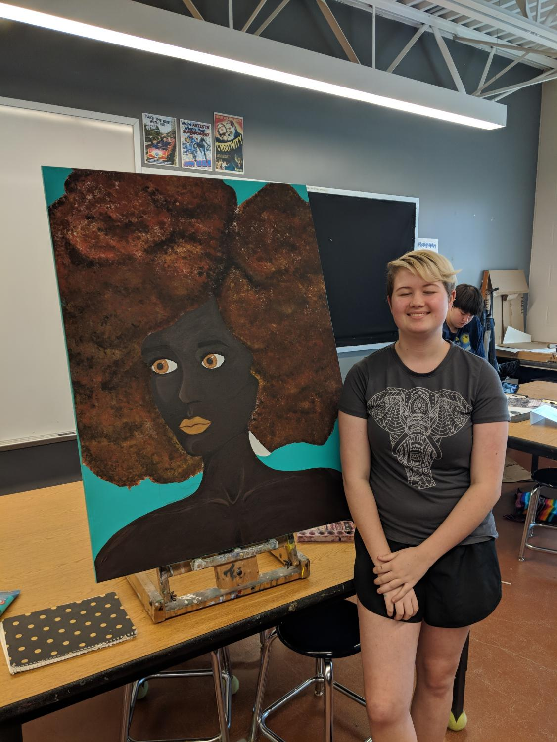 Gillian Geist shows off one of her pieces that she created in the AP Studio Art class.
