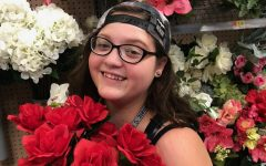 Kaitlyn Weeks poses for a photo with flowers while hanging out with her friends.
