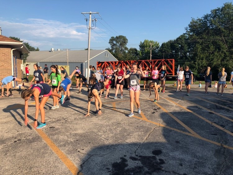 The+Girls%E2%80%99+Cross+Country+team+stretches+together+before+running+Run+with+Carl.