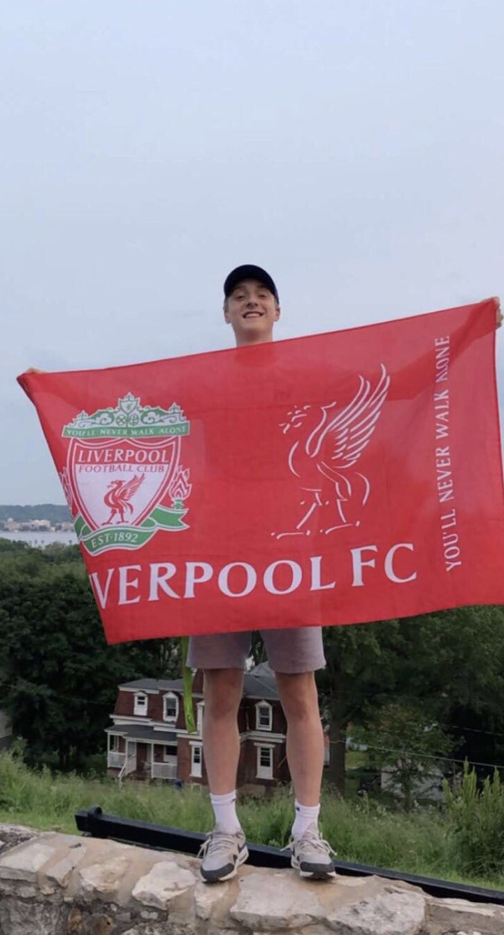 Spencer Brecht holding the flag of his favorite EPL team, Liverpool.