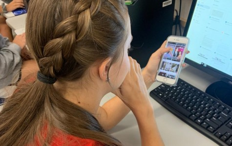 Senior Morgan McCartney checks her phone during a class.