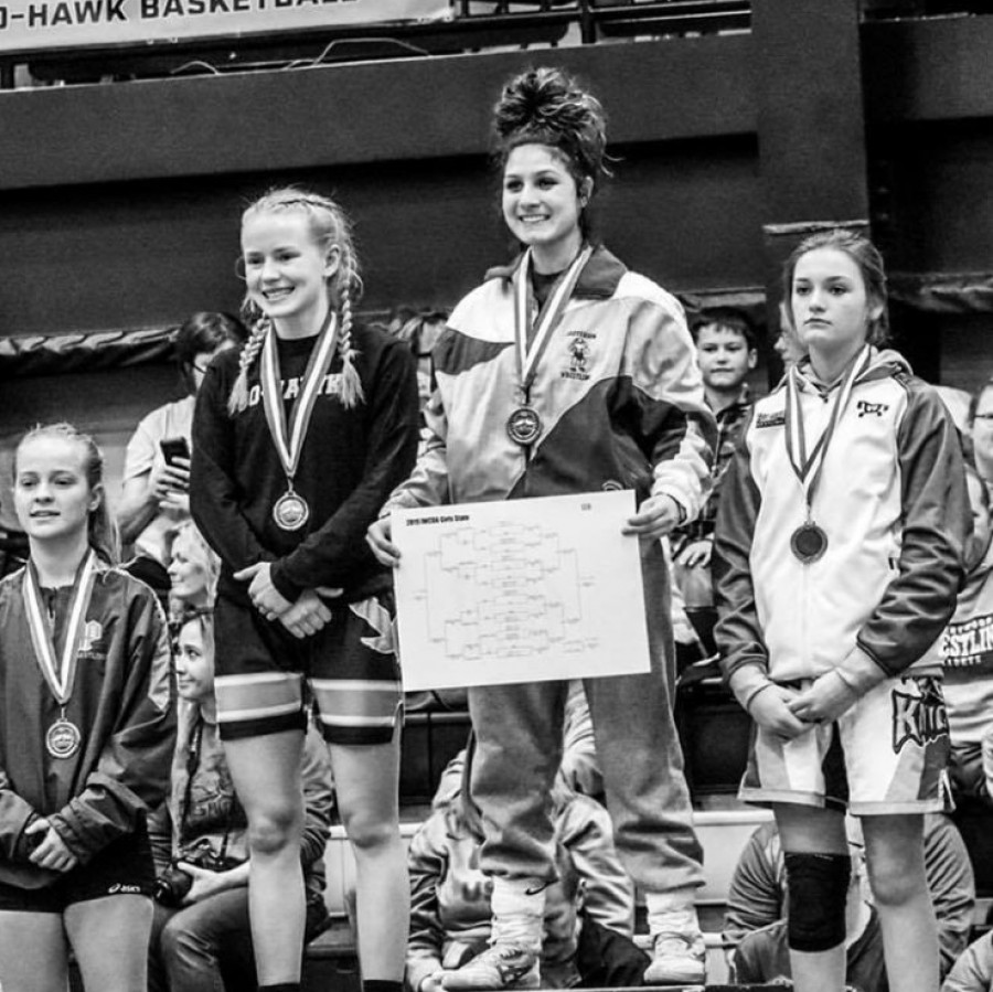 Chloe+Clemons+stands+atop+the+podium+as+champion+at+the+first+Iowa+girls+state+wrestling+tournament+in+Waverly%2C+Iowa+on+January+19%2C+2019.