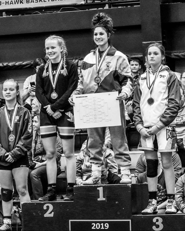 Chloe Clemons stands atop the podium as champion at the first Iowa girls state wrestling tournament in Waverly, Iowa on January 19, 2019.