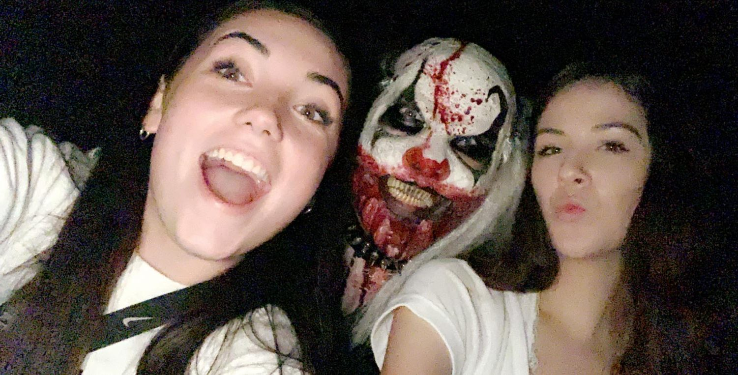 Senior Caitlin Crome and her friend pose with an actor at a local haunted house. While the actor's mask is terrifying, the two know they are in no real danger.