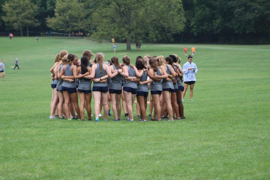 The+JV+girls+cross+country+team+huddles+together+to+motivate+each+other+before+their+race+in+Peoria+on+September+21st.+