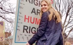 Alumni Lily Williams proudly displays her poster atop the Department of Justice sign, hoping to get a better view of the speakers at the Women's March in Washington D.C. Williams is an avid supporter of women's rights, including the right to vote.