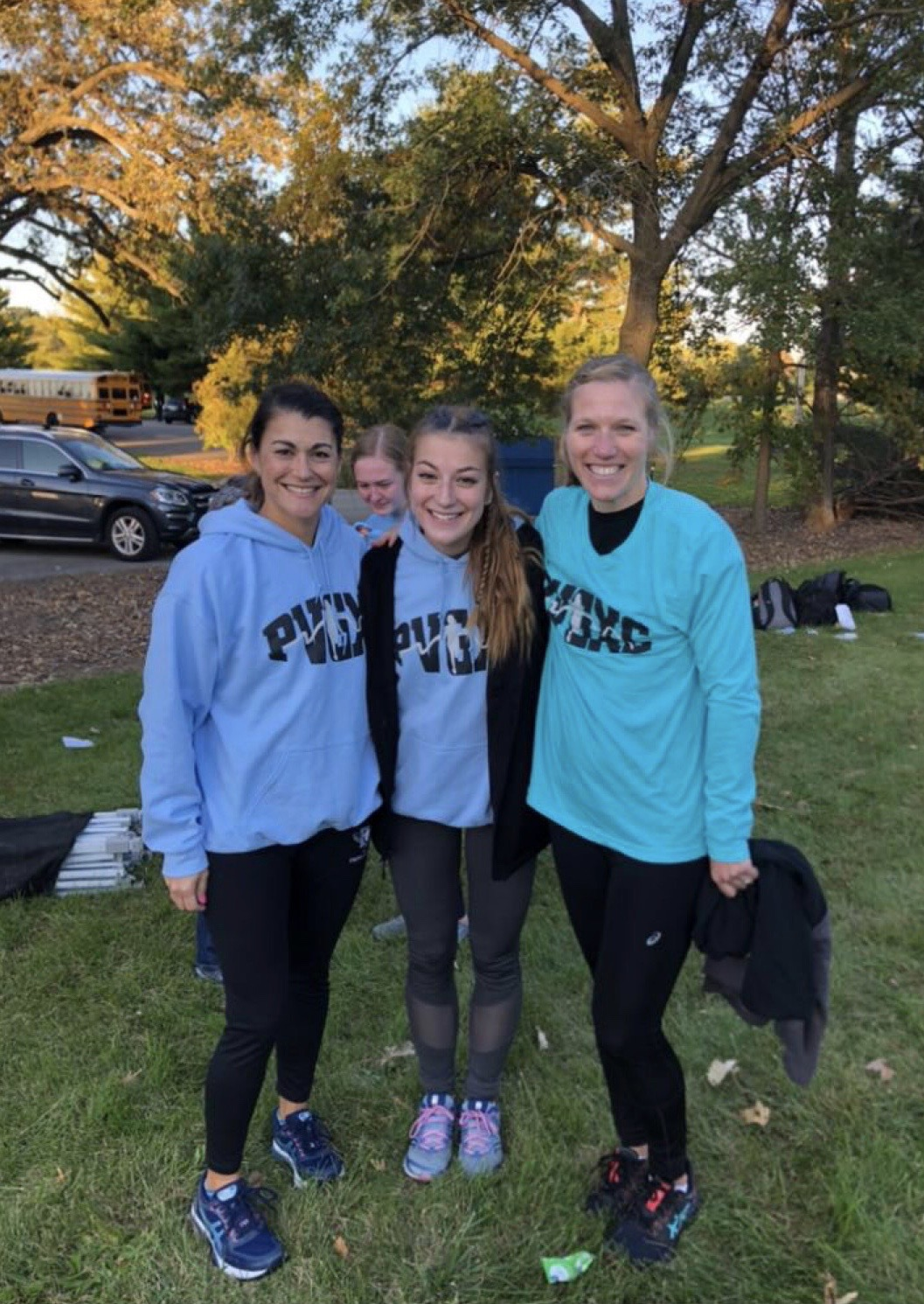 Senior Clare Basala stands amongst her female cross country coaches who have taught her about self-acceptance in the sport of running.