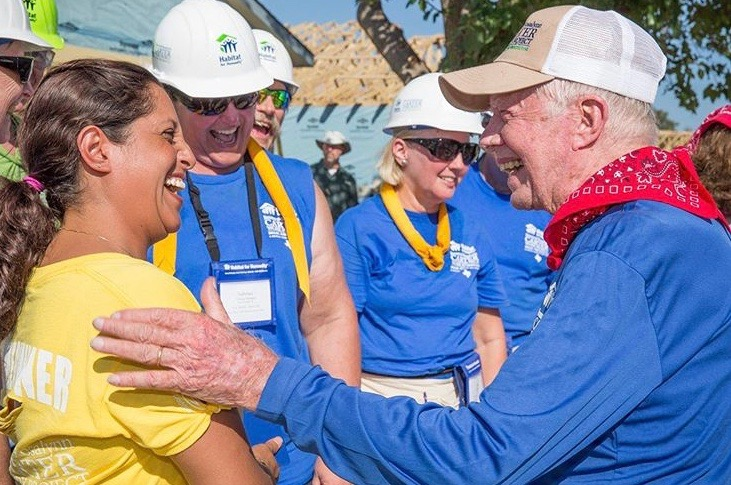 Former President Jimmy Carter talking with a group of people during the Carter Project.