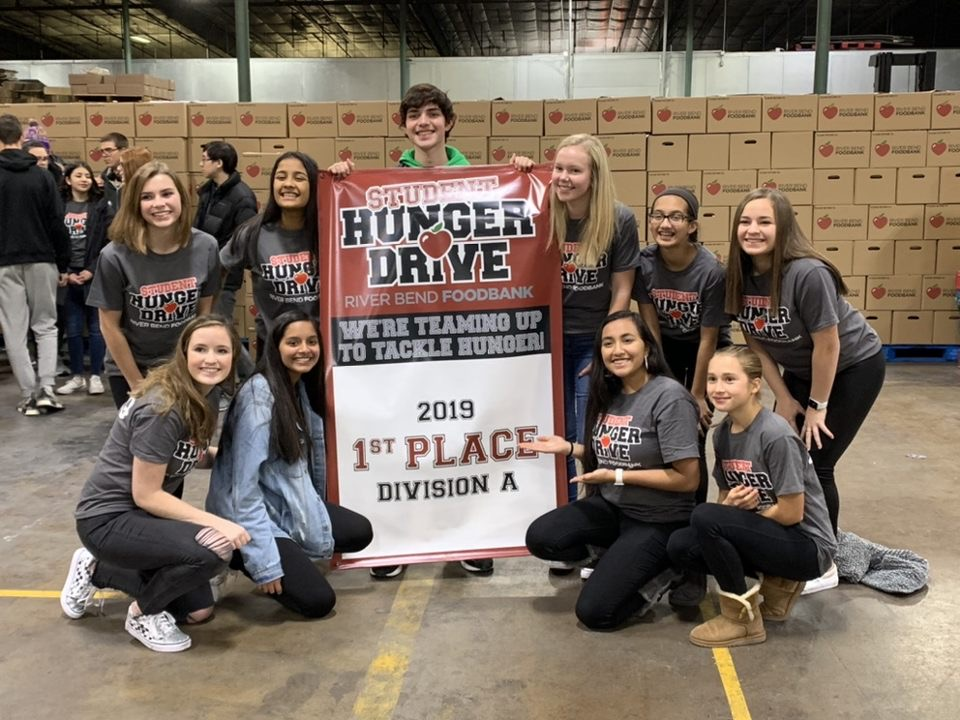 Spartan Assembly members show off their banner at the River Bend Foodbank after being awarded 1st place in the 2019 Division A Student Hunger Drive.
