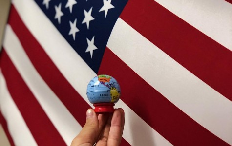 Senior Cienna Pangan holds a globe in front of the United States flag to represent the importance of focus on world news rather than just national news.