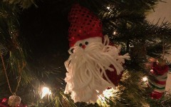 A Santa-themed ornament hangs from a Christmas tree.