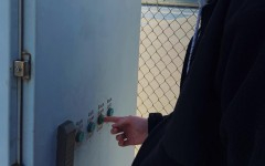 Senior Anthony Cox pushes a button to turn on the tennis court lights on his desired court after paying a fee.