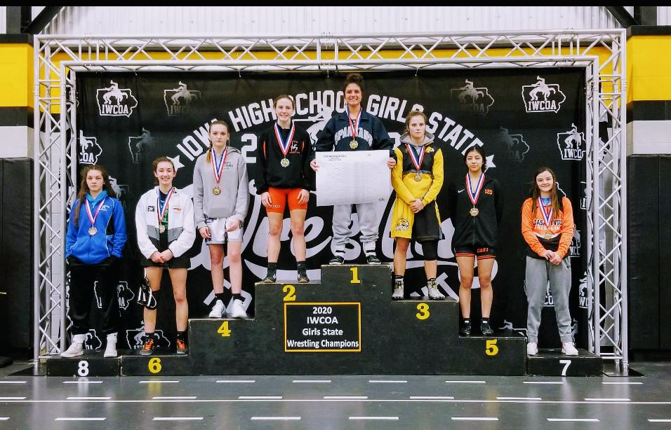 Senior Chloe Clemons celebrates her 120 pound state championship on top of the podium at Waverly Shell-Rock High School on Jan. 25, 2020.